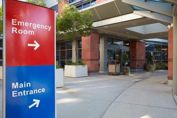 Entrance to a hospital with signs pointing to emergency room and main entrance