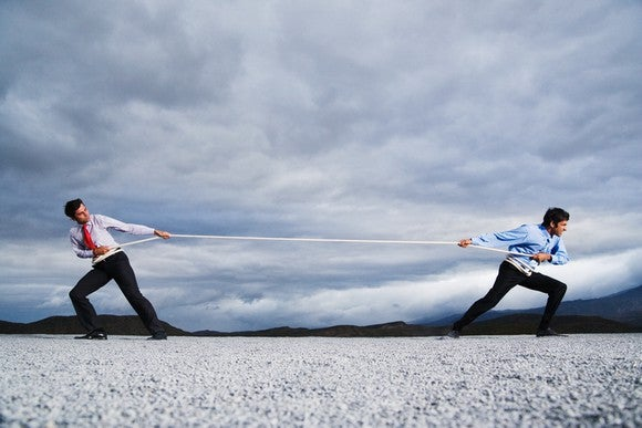 Two businessmen engaged in a game of tug-o-war with a rope.