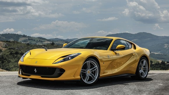A yellow Ferrari 812 Superfast, a low-slung and sharply-styled two-seat sports car.