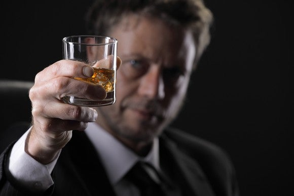 Man in suit holding up glass of whiskey