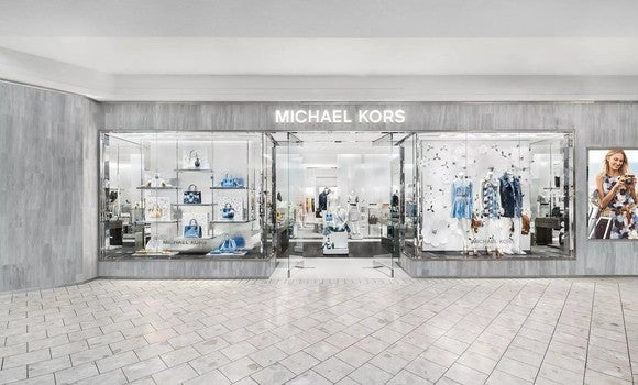 Silver-tone Michael Kors store location as seen from interior of mall.