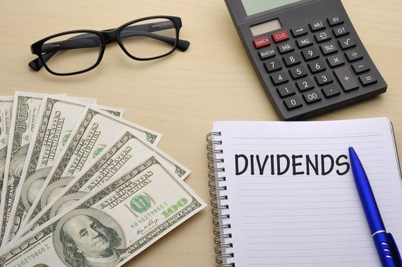 Cash, glasses, calculator, and notebook marked Dividends on a flat surface.