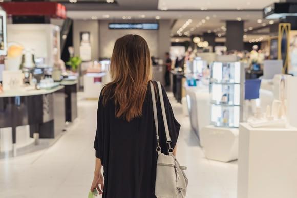 Woman walking into high-end fashion retail store