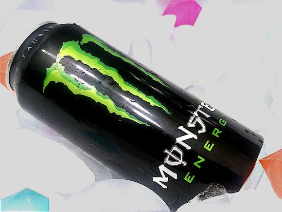 A can of Monster Energy resting on ice cubes and colorful plastic drink-cooler gems.