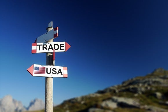 """Road signs with """"Trade"""" and """"USA"""" facing opposite directions"""