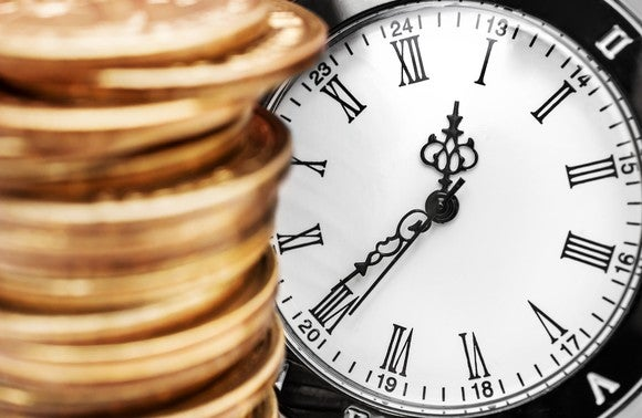 A stack of gold coins in front of a clock.