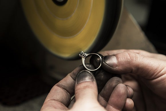 Jeweler polishing a diamond ring.