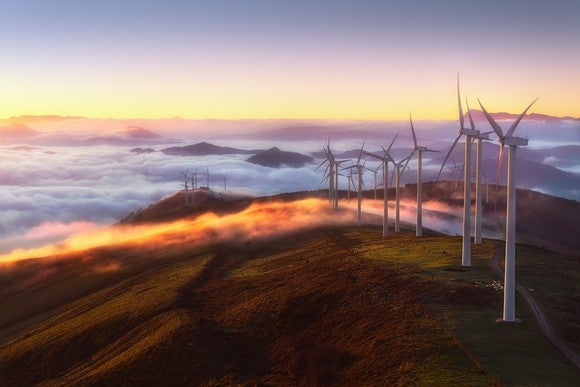 A row of wind turbines stretch across a mountain ridge as fog blankets the landscape behind it.