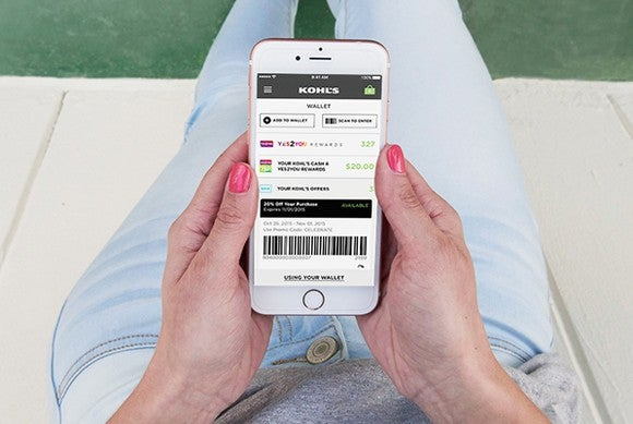 A person holds a smartphone with the Kohl's app loaded.