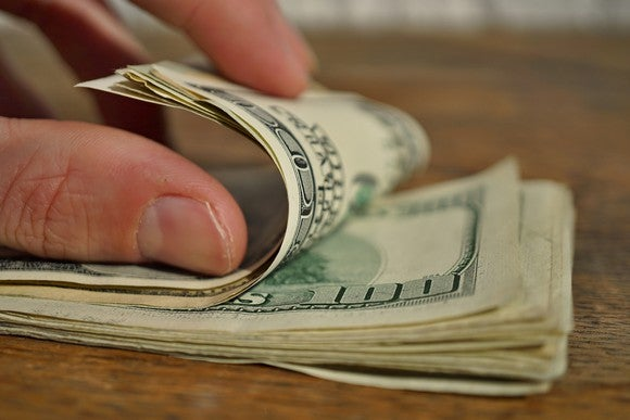 A hand counting a stack of $100 bills.