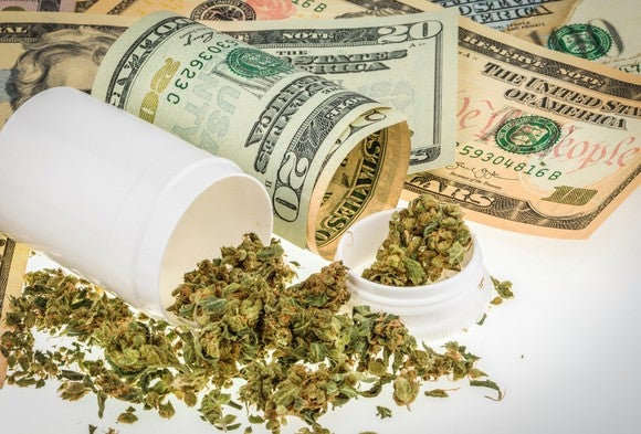 Plastic bottle with cannabis spilling out next to U.S. $20 bills.