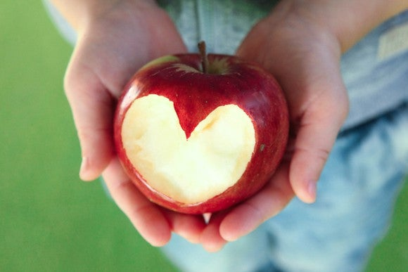 Someone holding an apple with a heart shape cut out of it.