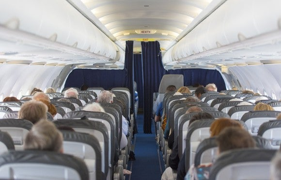 People are seated on a plane.