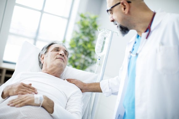 Older male patient lying down while doctor pats him on the shoulder