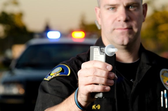 A peace officer holding a breathalyzer device in his right hand.