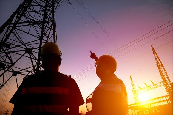 Two worker watching the power tower and substation with sunset background.