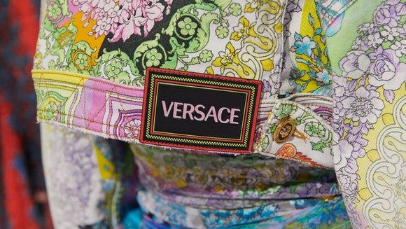 A close-up of a Versace label stitched to a piece of multicolored clothing.