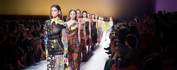 A line of models walking at a Versace runway show.