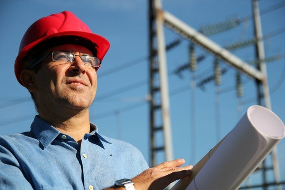 A man holding blueprints with a high voltage power line behind him