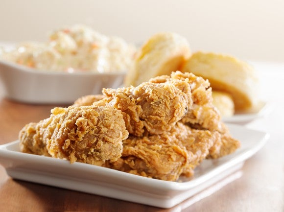 A handful of fried chicken pieces with biscuits on the side.