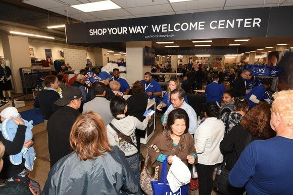 Customers crowd a welcome center at a Sears store