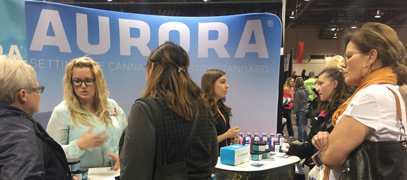 Several people at a convention talking to representatives at a booth with the Aurora banner and products on a table.