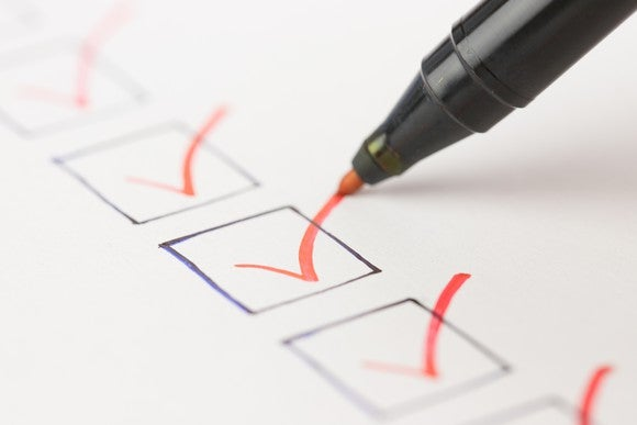 Pen checking boxes on checklist.
