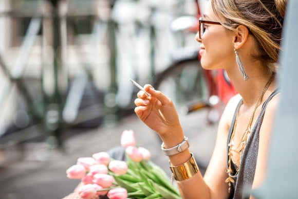 A woman smoking a joint while sitting outside next to a bouquet of flowers.