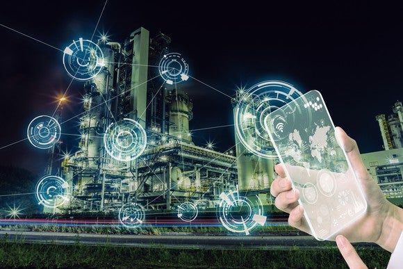 A factory with digital symbols overlaid, and a hand holding a transparent smartphone