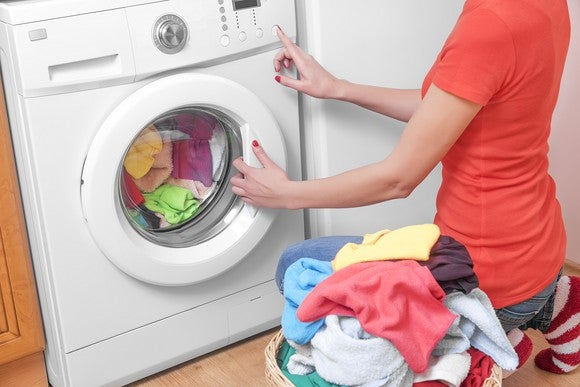 A woman unloading clean laundry from the dryer.