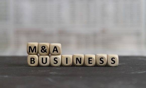 The words M&A business spelled out in wooden blocks.