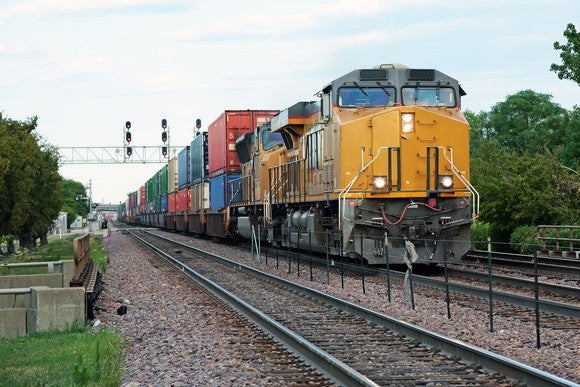 Two yellow locomotives pulling a double-stacked freight train.