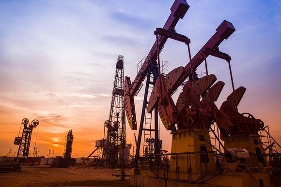 An oil pumping unit with the sun setting in the background.