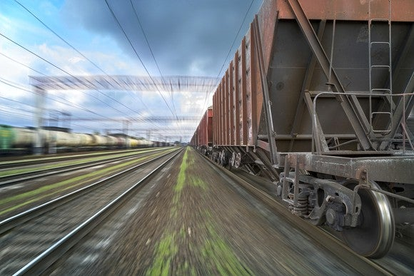 Freight train with top-loaded cars passing viewer in a blur.