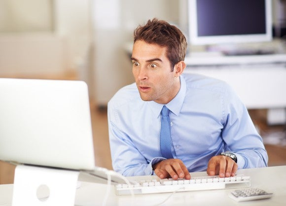 A man in a business shirt and tie with his eyes wide open and a surprised look on his face staring at a computer monitor.
