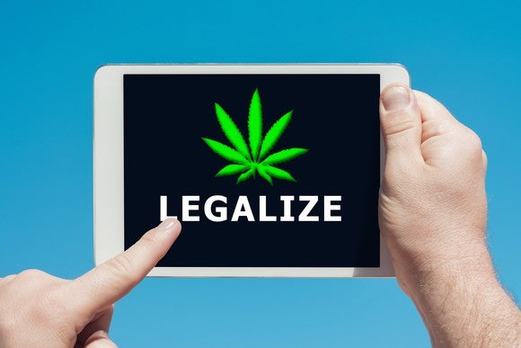 A person holding a tablet and touching the screen which says legalize, with a cannabis leaf above the word.