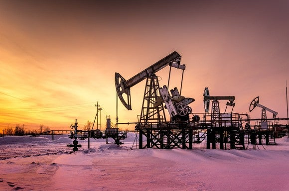 A oil pump at sunset with snow on the ground.