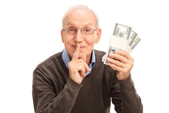 A senior man holds his finger to his lips while holding three stacks of banded hundred dollar bills.