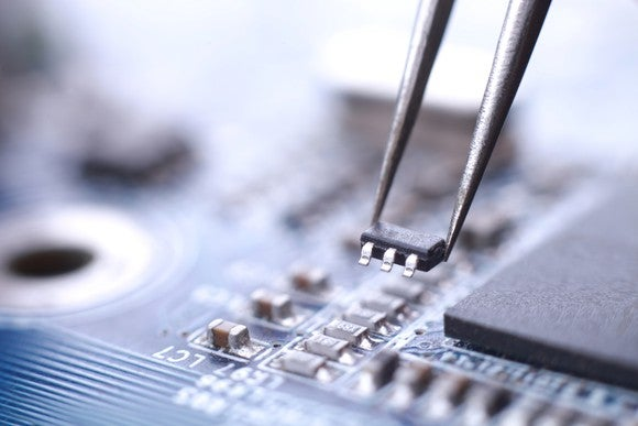 Technician using tweezers to install a microchip on a circuit board.