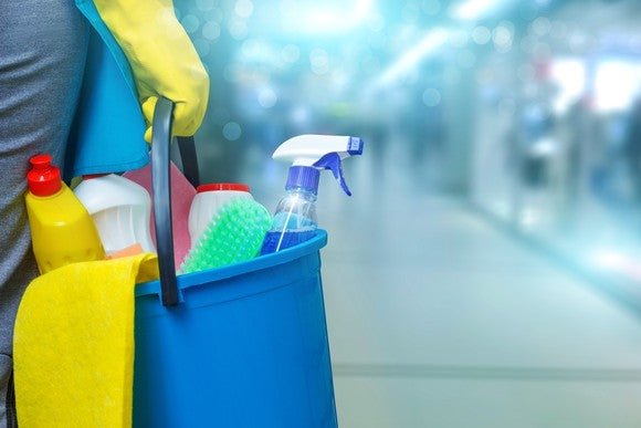 A cleaning person holds a bucket of cleaning products.