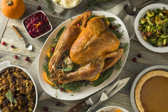 Large cooked turkey surrounded by side dishes.