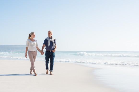 An older couple walks on a beach.