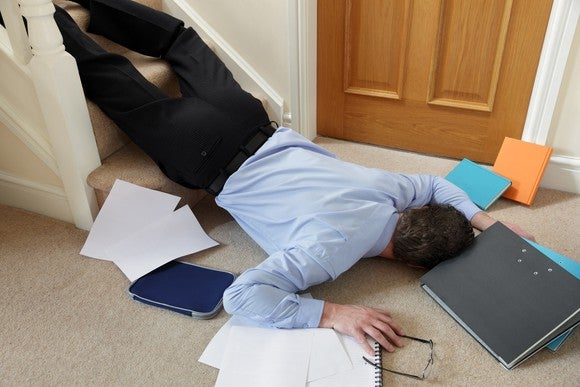 A man lies sprawled at the foot of some stairs, his notebook, tablet, and papers scattered around him.