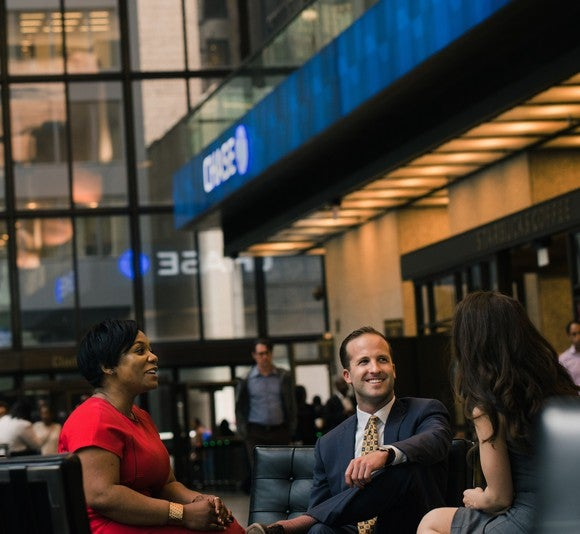 Three people talking around a table in the lobby of a building with the Chase logo in it.