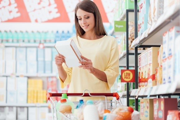 Woman in dollar store aisle reading label on cereal box.