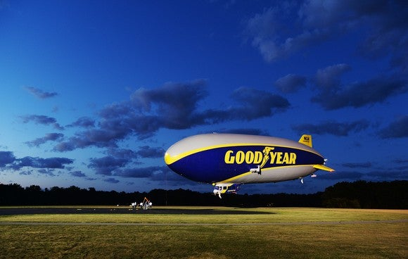 A Goodyear blimp landing in a field in the evening.