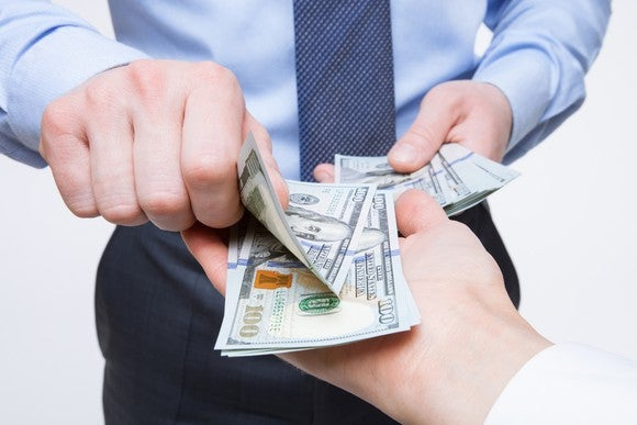 The hands of a man in a business shirt and tie exchanging money with someone else's hand.