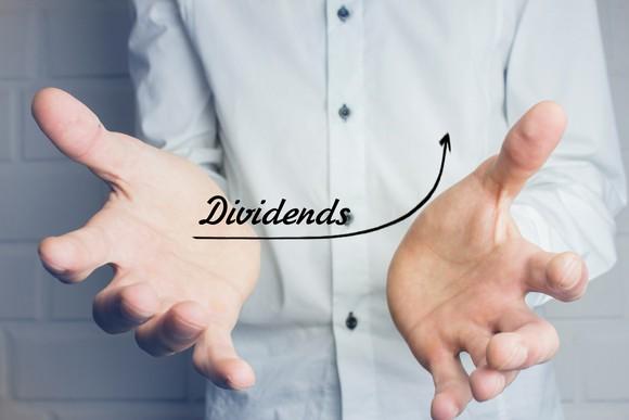 A chart of rising dividends between a man's hands.