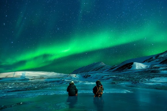 People stand before a stunning display of the aurora borealis in Alaska.