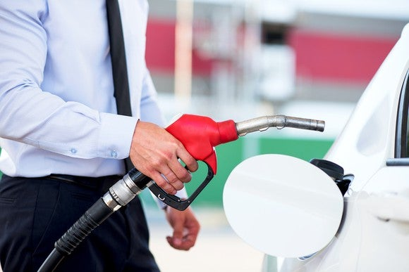 A man prepares to place a fuel nozzle in his car.